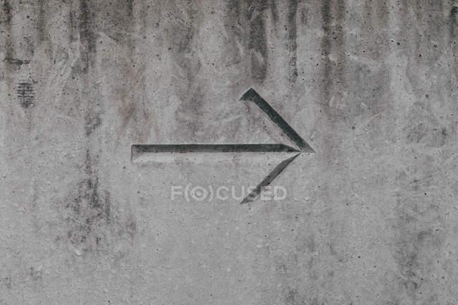 Arrow on concrete wall — Stock Photo