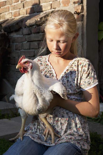 Gallo della holding della ragazza mentre sedendosi vicino fienile — Foto stock