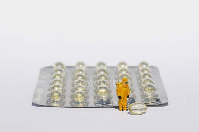 Pequeño científico en juego limpio examinar gel cápsulas de blíster - foto de stock