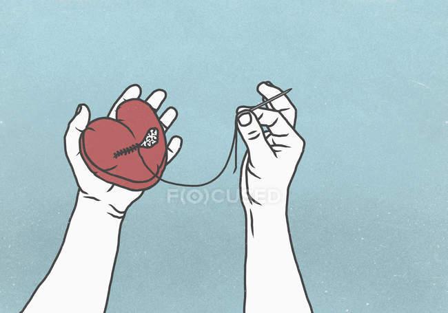 Руки шьют разбитое сердце иголкой и ниткой — стоковое фото