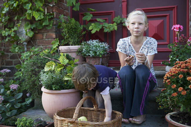 Girls sitting among flowerpots on front stoop — Stock Photo