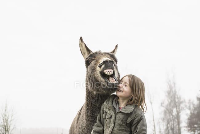 Jeune fille espiègle et âne pendant la journée — Photo de stock