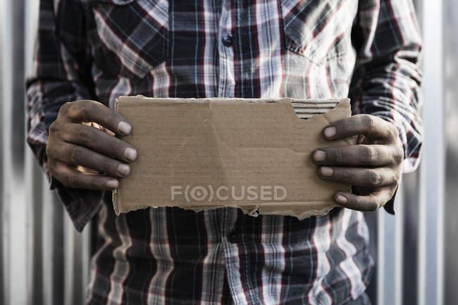 Бездомный держит картонную табличку — стоковое фото