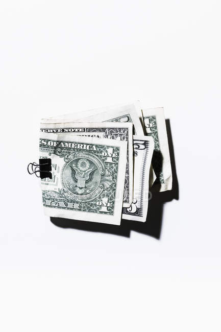 Clip holding folded one and five dollar bills — Stock Photo