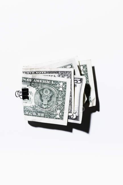 Clip que sostiene un doblado y billetes de cinco dólares - foto de stock