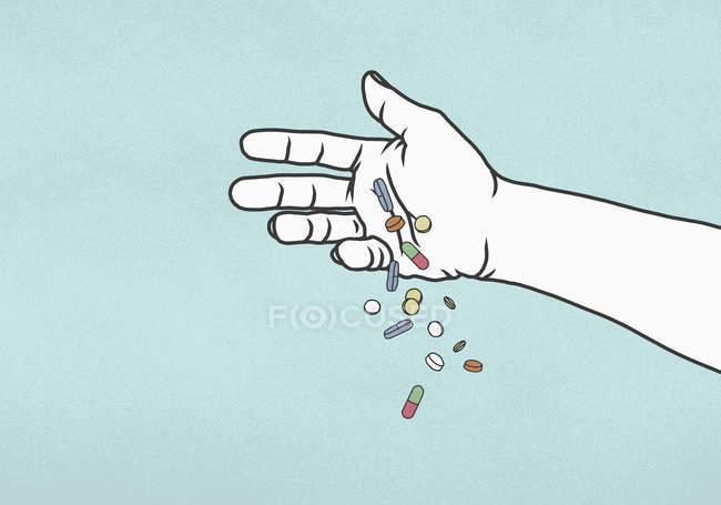 Mano caer píldoras sobre fondo azul - foto de stock
