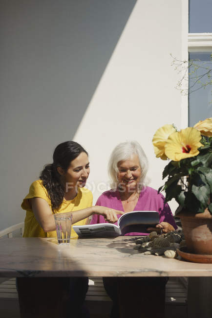 Senior mother and daughter reading magazine on sunny patio — Stock Photo