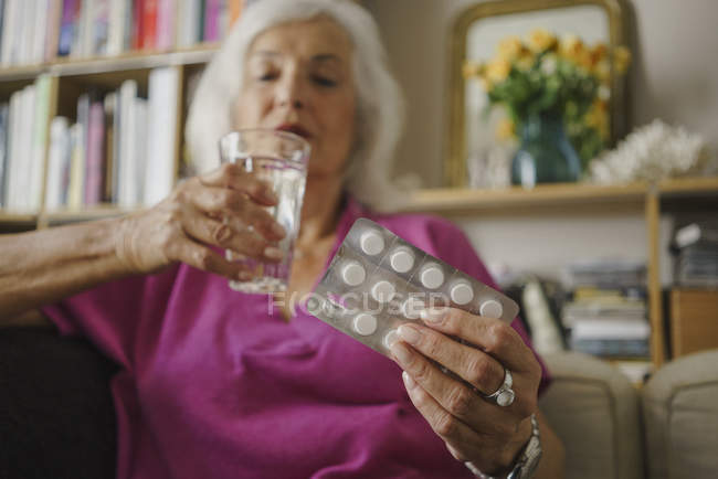 Senior woman taking medication — Stock Photo