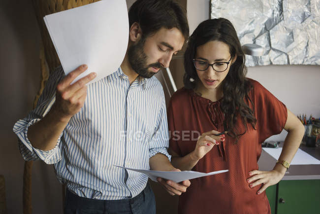 Businessman and businesswoman reviewing paperwork in office — Stock Photo