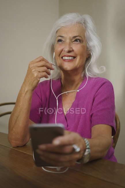 Усміхаючись старший жінка слухати музику з навушниками і mp3-плеєр — стокове фото