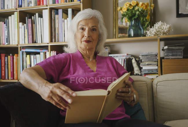 Portrait confident senior woman reading book in living room — Stock Photo