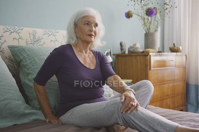 Senior woman relaxing on bed — Stock Photo