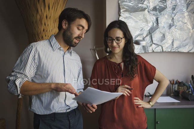Businessman and businesswoman discussing paperwork in office — Stock Photo