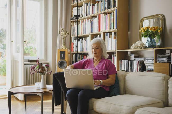 Senior woman using laptop on living room sofa — Stock Photo