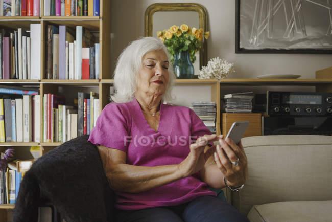 Senior woman using smart phone on living room sofa — Stock Photo