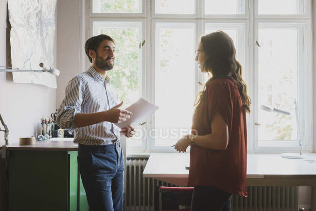 Businessman and businesswoman talking in office — Stock Photo