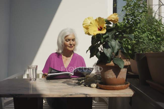 Senior woman reading magazine on sunny patio — Stock Photo