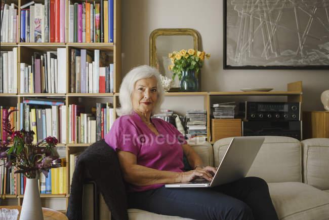 Портрет уверенной пожилой женщины с помощью ноутбука на диване гостиной — стоковое фото