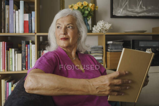 Thoughtful senior woman reading book — Stock Photo