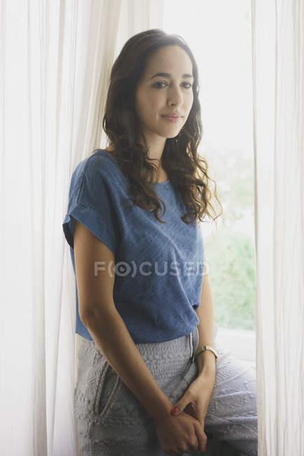 Serene woman at window — Stock Photo