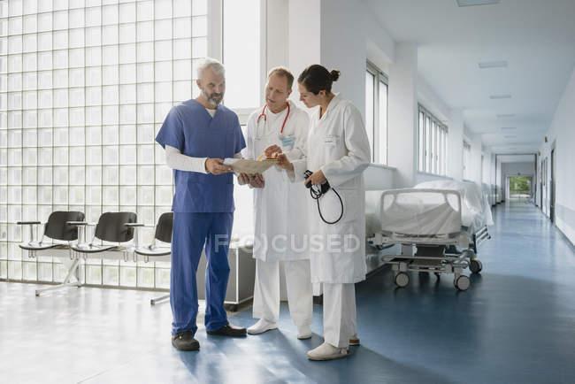 Врачи обсуждают медкомиссии в больничном коридоре — стоковое фото