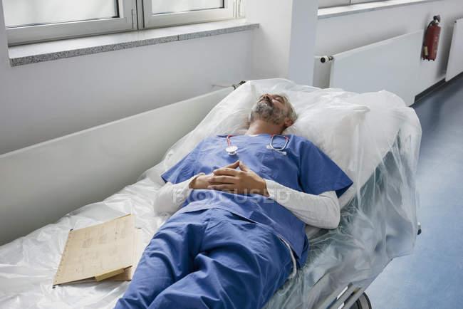 Исчерпаны доктор отдыхает, спать на носилках в больничном коридоре — стоковое фото