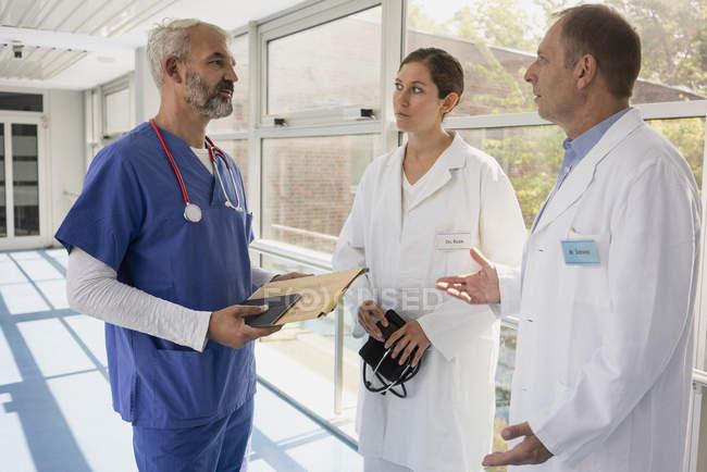 Врачи говорят в коридоре больницы — стоковое фото