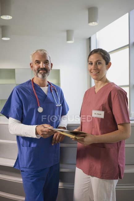 Médicos seguros de retratos con historia clínica en el hospital - foto de stock