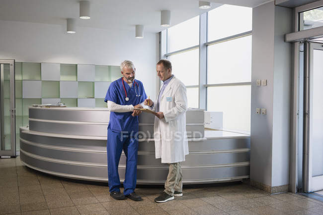 Male doctors discussing medical record in hospital — Stock Photo
