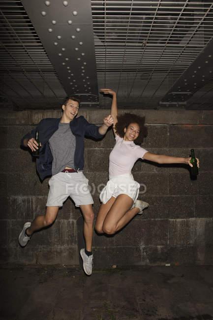Coppie giovani esuberante ritratto bevendo birra e salto — Foto stock