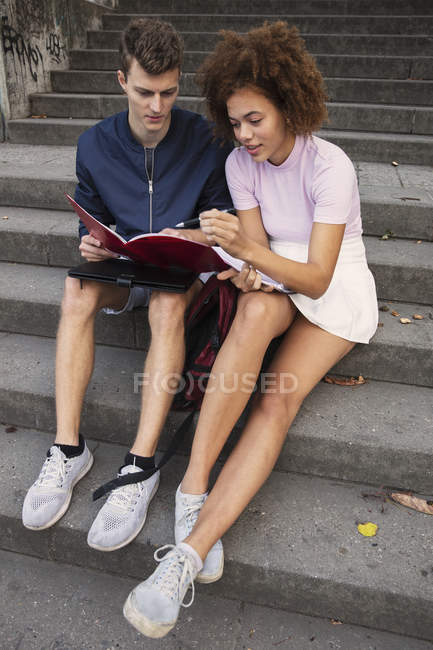 Young couple reviewing paperwork on steps — Stock Photo