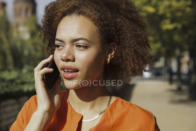 Young woman talking on smart phone on sunny sidewalk — Stock Photo