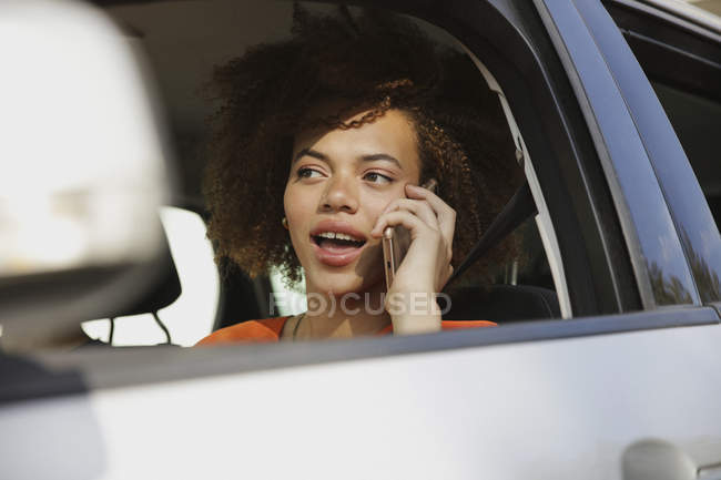 Young woman talking on smart phone and driving car — Stock Photo