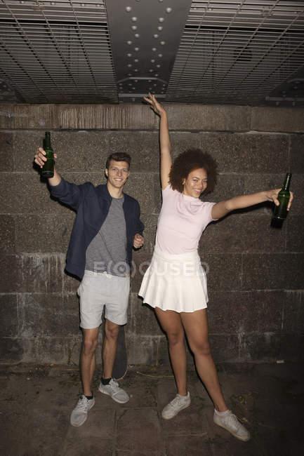 Coppie giovani esuberante ritratto bere birra nel seminterrato — Foto stock