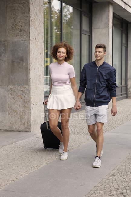 Jeune couple avec valise marchant sur le trottoir urbain — Photo de stock