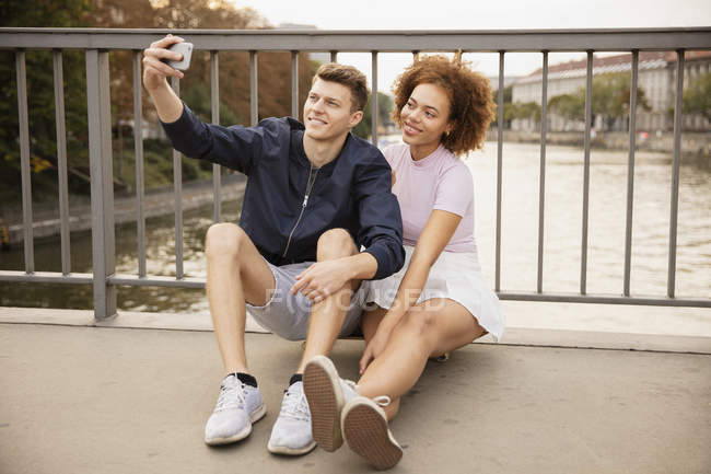 Young couple taking selfie with camera phone on urban bridge — Stock Photo
