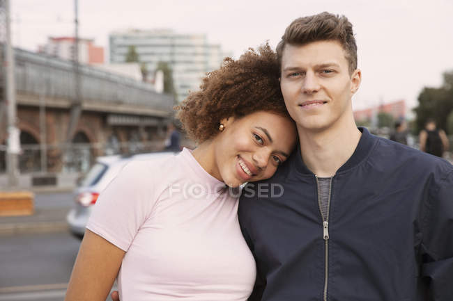 Portrait affectionate young couple on urban sidewalk — Stock Photo