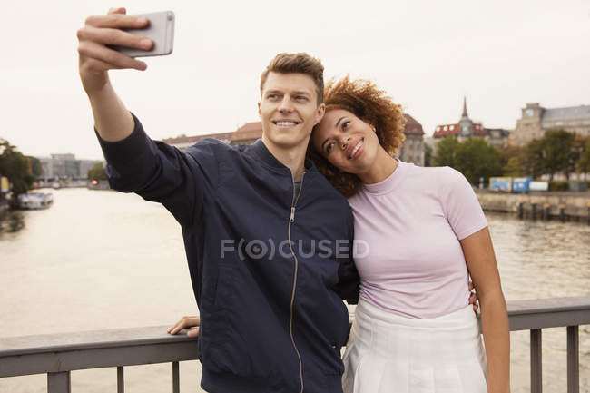 Affectionate young couple with smart phone taking selfie on urban bridge — Stock Photo