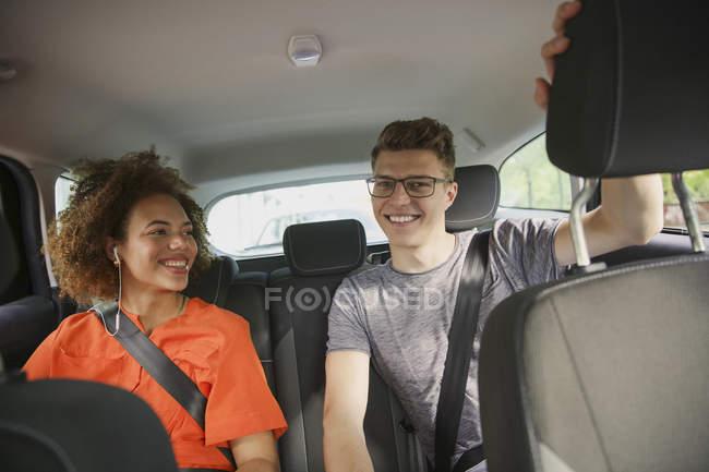 Felice giovane coppia cavalcando nel sedile posteriore della macchina — Foto stock