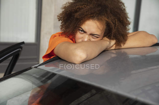 Portrait young woman squinting, leaning on car — Stock Photo