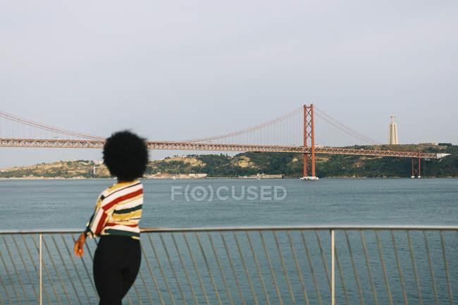 Mujer joven parada frente al mar, mirando el Puente 25 de Abril y la Estatua de Cristo Rei, Lisboa - foto de stock