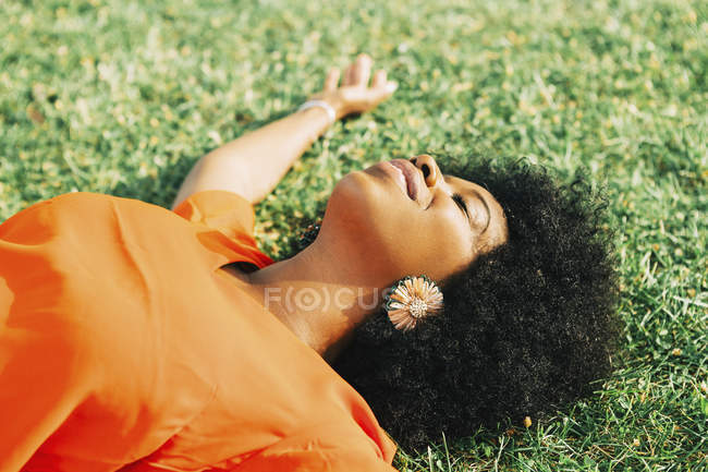 Carefree, serene young woman laying in sunny grass — Stock Photo