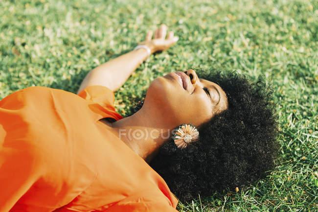 Беззаботная, спокойная молодая женщина, лежащая в солнечной траве — стоковое фото