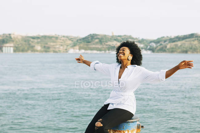 Carefree young woman with arms outstretched at waterfront, Belem, Lisbon, Portugal — Stock Photo