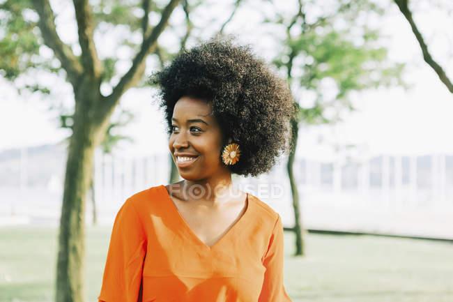 Confiante, sorrindo jovem no parque ensolarado — Fotografia de Stock