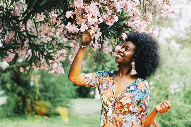 Giovane donna in piedi sotto l'albero con fiori rosa — Foto stock