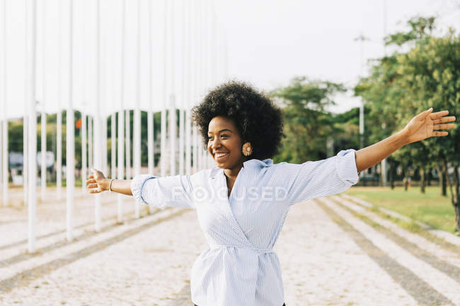 Carefree young woman with arms outstretched in sunny park — Stock Photo