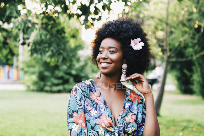 Happy young woman with pink flower in hair — Stock Photo