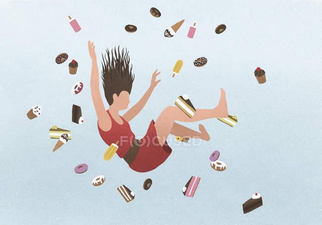 A woman falling amongst sweet junk food — Stock Photo