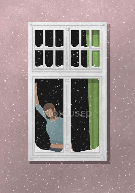 Uma mulher em pé junto a uma janela com neve a cair do lado de fora — Fotografia de Stock